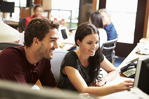 Two Colleagues Working At Desk With Meeting In Background